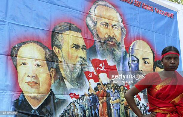 Activists from the Communist Party of India MarxistLeninist stand in front of a poster of International Communist Party leaders as they listen to a...