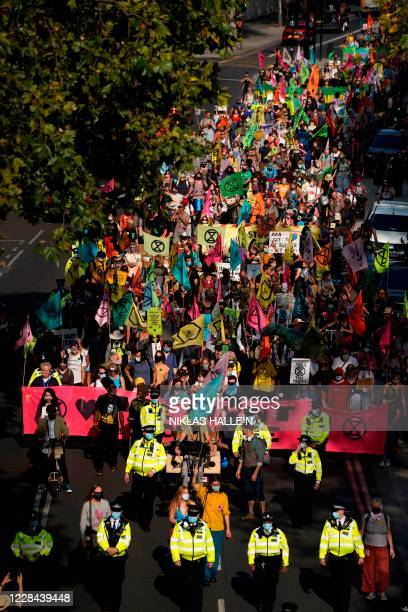 Activists from the Extinction Rebellion climate change group march at a demonstration in London on September 10 2020 on the final day of their new...