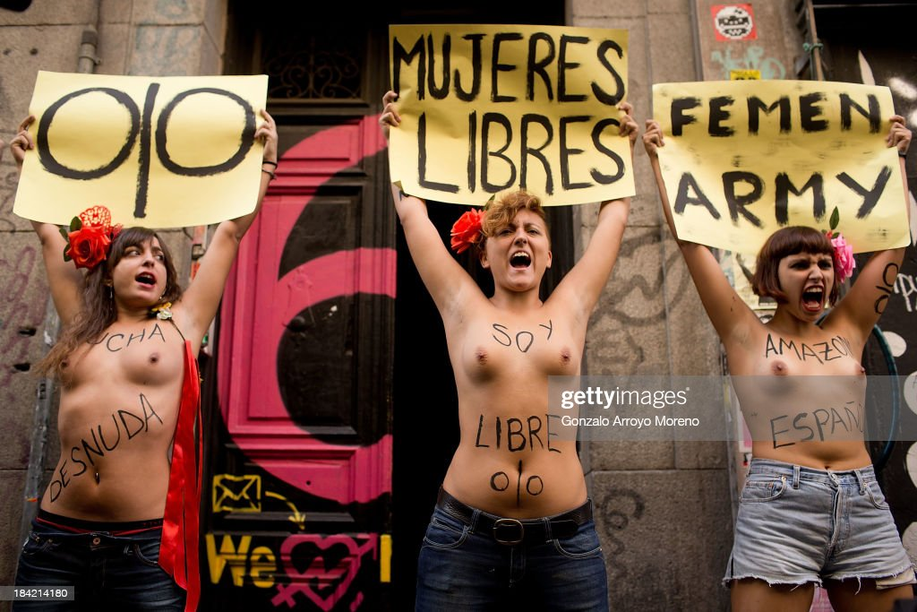 Activists from the feminist group FEMEN protest at the front door of Patio Maravillas where they have placed their headquarters with femenist sings during their official Opening on October 12, 2013 in Madrid, Spain.