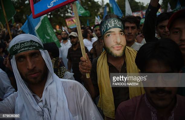 Activists from the Jamaat e Islami Pakistan organisation wear masks bearing the image of Burhan Wani the 22yearold Hizbul Mujahideen commanded killed...