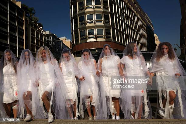 Activists from the Lebanese NGO Abaad a resource centre for gender equality dressed as brides and wearing injury patches hold a protest in downtown...