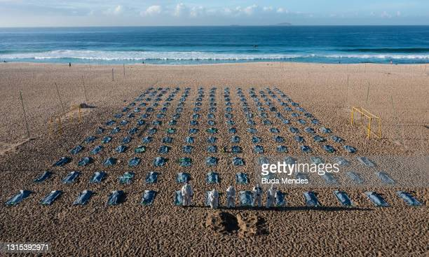 """Activists from the NGO """"Rio de Paz"""" stand on Copacabana beach where they placed symbolic body bags and dug mock graves during an event to pay homage..."""