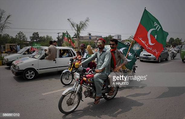 Activists from the Pakistan Tehreek-e-Insaf ride a motorcycle bearing party flags at the start of the Tehrik-e-Ehtesab rally in Peshawar on August 7,...