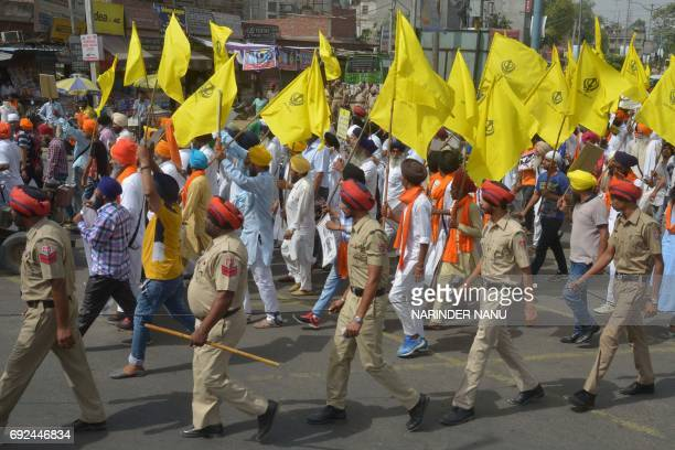Activists from the Sikh-centric political party Shiromani Akali Dal hold placards and religious flags during a march on the eve of the 33th...