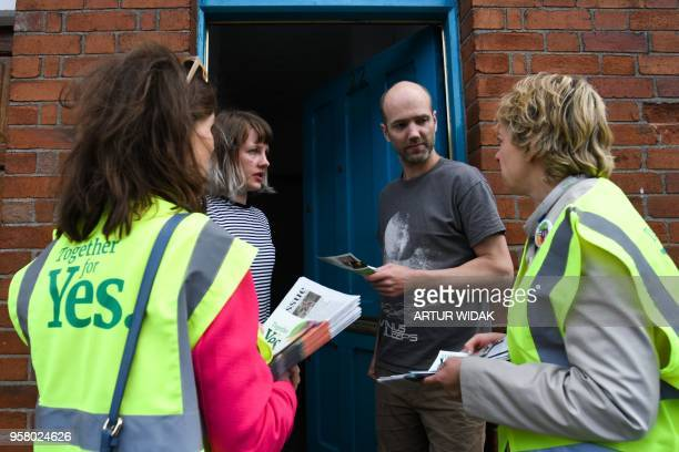 Activists from the 'Together for Yes' campaign speak to a couple on their doorstep as they canvass for a 'yes' vote in the referendum to repeal the...