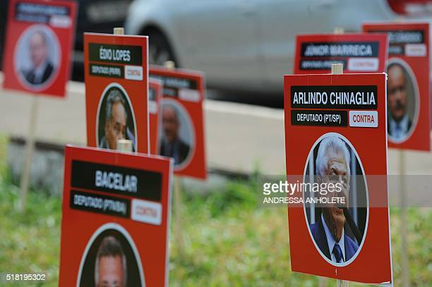 """Activists from the """"Vem Pra Rua"""" opposition movement protest placing placards with portaraits of lawmakers in front of the Congress in Brasilia..."""