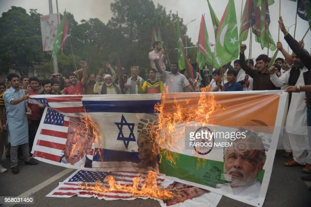 Activists from the Wahdat Muslimeen Pakistan organisation burn a banner bearing the images of Indian Prime Minister Narendra Modi Israeli Prime...