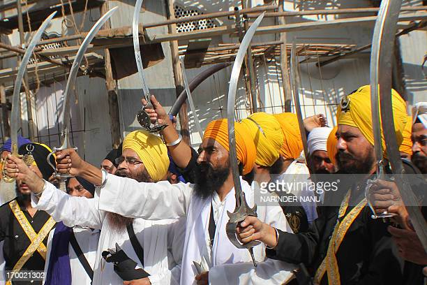 Activists from various radical Sikh organisations hold swords in support of Sikh leader Sant Jarnail Singh Bhindranwale and Khalistan, the name given...