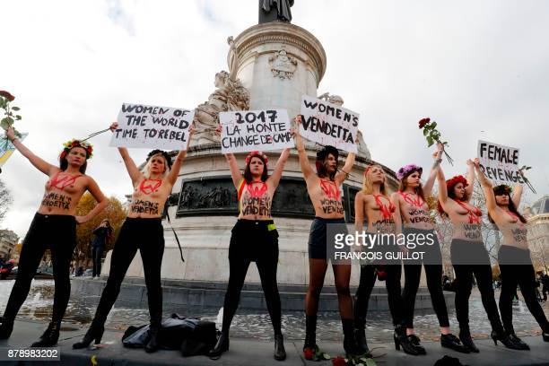 TOPSHOT Activists from women's rights movement Femen including leader Inna Shevchenko stand topless while holding signs on the Place de la Republic...