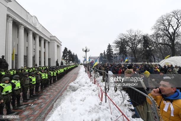 TOPSHOT Activists gather opposite security personnel during a mass march and rally calling for the impeachment of Ukrainian president Petro...
