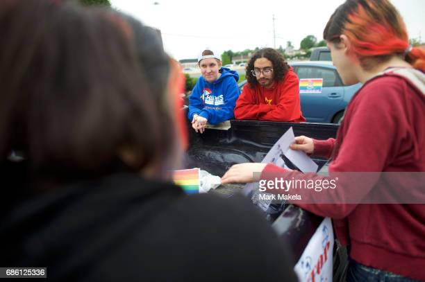 Activists gather to affix protest posters against the Klu Klux Klan to their cars before driving in a caravan through the Quarryville area, where the...