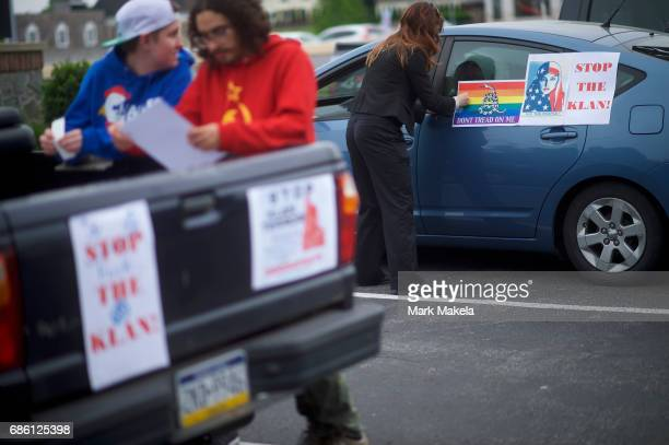 Activists gather to affix protest posters against the Klu Klux Klan to their cars before driving in a caravan through the Quarryville area where the...