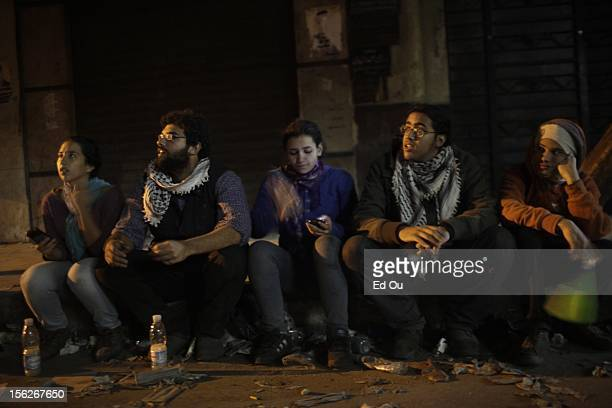 Activists Hana ElRakhawi Omar Shamy Menna Elshishini and Hossam Shukrallah 19 sit on the curb in Cairo Egypt as clashes with the police continue a...