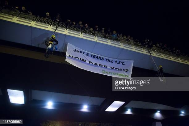 Activists hang a banner to raise awareness about climate change during the demonstration. Thousands of people from all over Europe protest in Madrid...