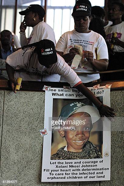 AIDS activists hang a portrait of the late Nkosi Johnson during his funeral service at a Johannesburg church Nkosi was the longest surviving child...