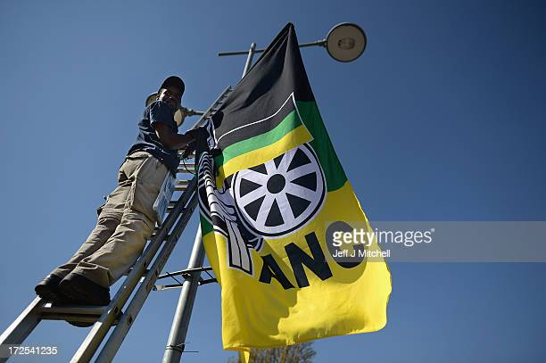 ANC activists hang flags on lamp post near the Vilakazi Street home of Nelson Mandela who is being treated for a recurring lung infection in hospital...