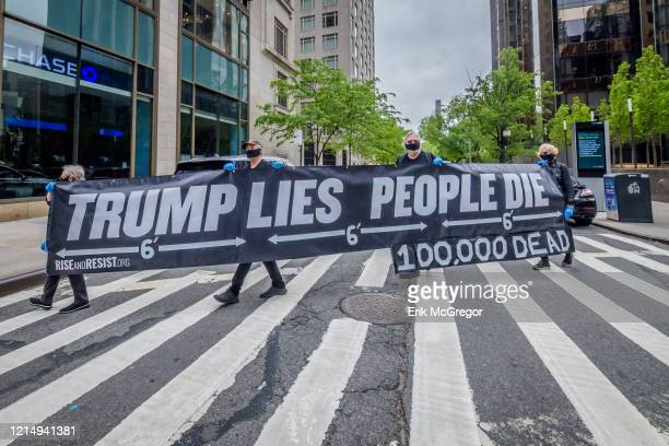 Activists held a banner that read TRUMP LIES PEOPLE DIE and 100000 DEAD outside Trump International Hotel and Tower In a somber procession members of...