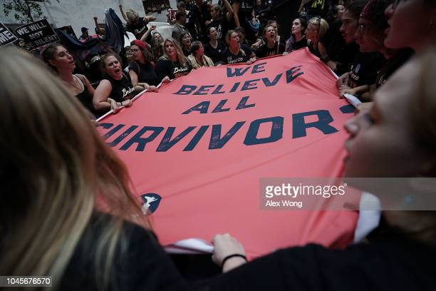 Activists hold a banner during a protest October 4, 2018 at the Hart Senate Office Building on Capitol Hill in Washington, DC. Activists are rallying...