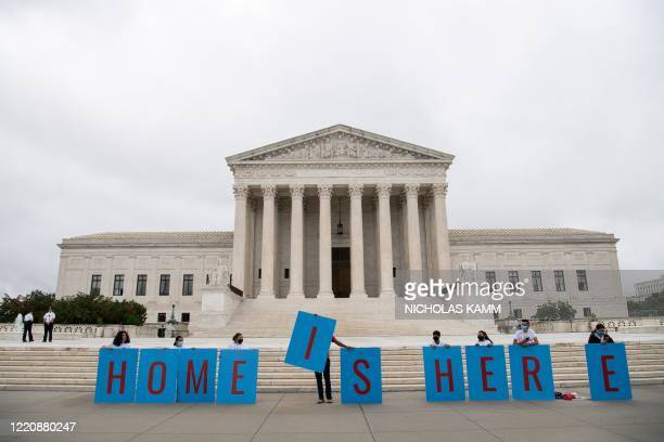 Activists hold a banner in front of the US Supreme Court in Washington DC on June 18 2020 The US Supreme Court rejected President Donald Trump's move...