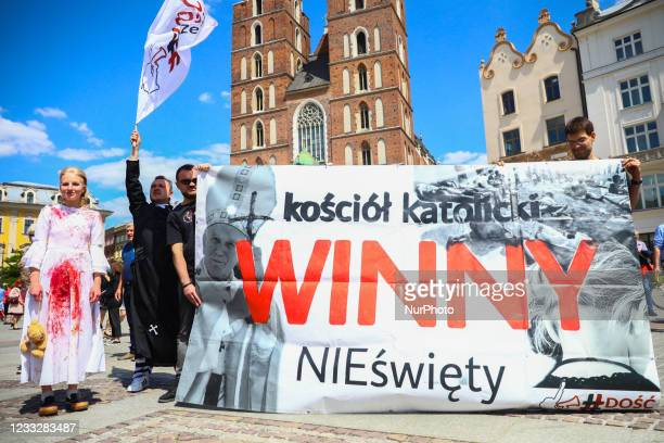 Activists hold a banner reading 'Catholic church guilty, not saint' protesting at the Main Square against the members of Polish catholic church...