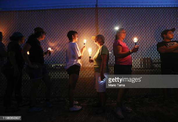 Activists hold a candlelight vigil at the perimeter fence securing the US Border Patrol station where lawyers reported that detained migrant children...