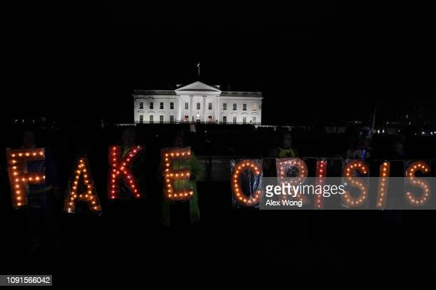 Activists hold a lit FAKE CRISIS sign as they stage a protest outside the White House in response to US President Donald Trump's prime time address...