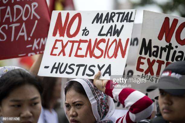 Activists hold a protest at the gate of the House of Representatives denouncing the Congress move to extend Martial Law in Mindanao in Manila on...