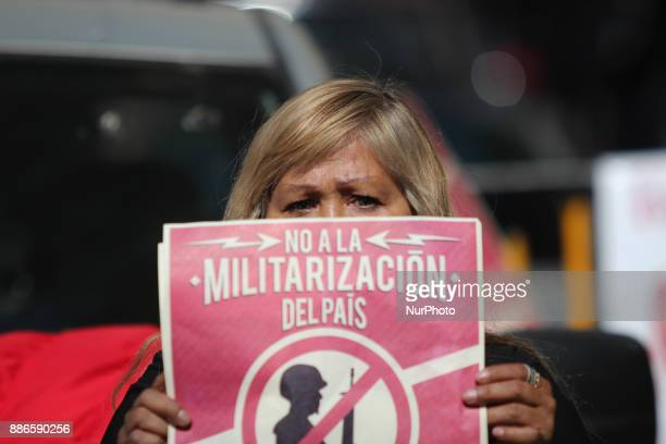 Activists hold banners against a law that militarises crime fighting in the country outside the Senate in Mexico City Mexico December 5 2017 Placards...