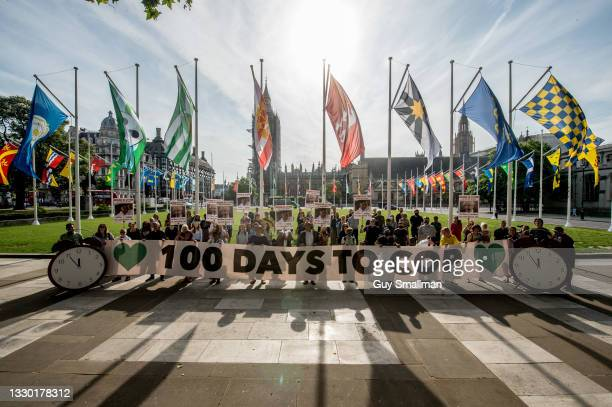 Activists hold banners and placards in Parliament square marking 100 days until the COP26 sumitt and demanding to know what action the Prime Minister...