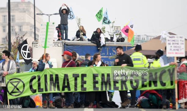 Activists hold banners and wave flags as they continue to block the road on Waterloo Bridge on the second day of an environmental protest by the...