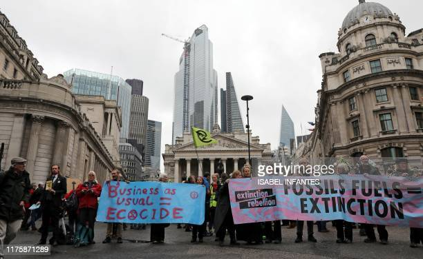 Activists hold banners as they protest outside the Bank of England and Royal Exchange during the eighth day of demonstrations by the climate change...