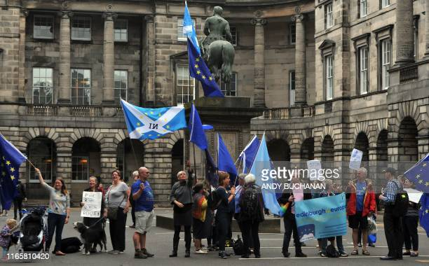 Activists hold EU and Scottish Saltire flags as they demonstrate outside of the Court of Session in Edinburgh on September 3 during a hearing in to...