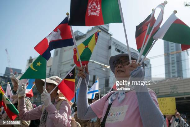 Activists hold flags during the Annual Earth Day in Shibuya district Tokyo on 21 April 2018 Environmental activists commemorated Earth Day with a...