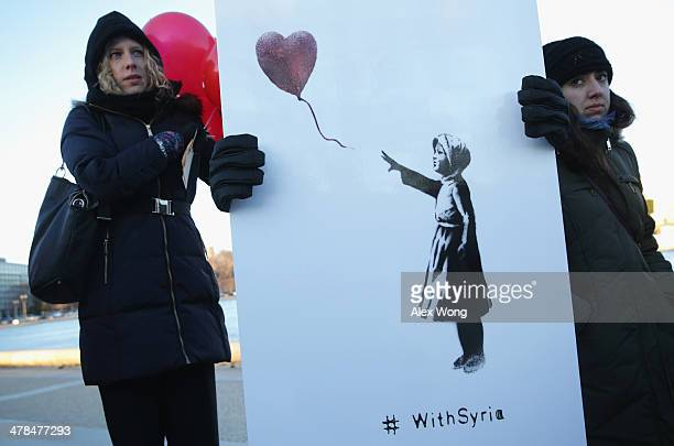 Activists hold graffiti artist Banksy's 'girl with the red balloon 'There is Always Hope'' mural during a 'vigil of solidarity' to mark the third...