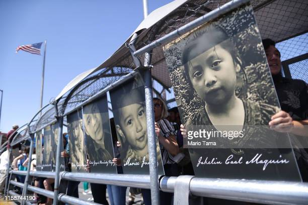Activists hold photos of migrant children who died trying to cross the USMexico border as they demonstrate standing on the Paso Del Norte Port of...