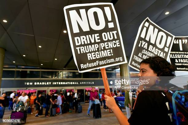 Activists hold placards as arrivals exit the hall at the International Arrivals section at Los Angeles International Airport on June 29 where free...