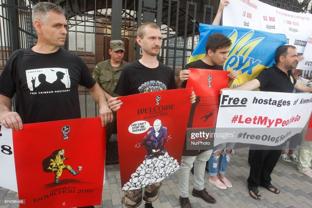 Activists hold placards by artist Andriy Yermolenko during a rally with an appeal to boycott the Russia World Cup 2018 football tournament, and demand the release Ukrainian director Oleg Sentsov and other Ukrainian political prisoners in Russia, near the Russian Embassy in Kiev, Ukraine, 14 June, 2018. Ukrainian film director Oleg Sentsov, who is serving a 20-year prison sentence in Russia, will have spent a month on hunger strike in jail demanding that Russia release his fellow Ukrainians who he says are being held as political prisoners. To draw Western attention to Moscow's role in the four-year conflict in eastern Ukraine, Ukrainian artist Andriy Yermolenko made a series of graphic drawings that have become popular.