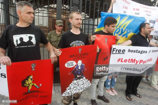 Activists hold placards by artist Andriy Yermolenko during a rally with an appeal to boycott the Russia World Cup 2018 football tournament and demand...