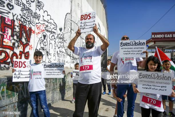 Activists hold placards calling for the boycott of Eurovision along Israel's controversial separation barrier which divides the West Bank from...