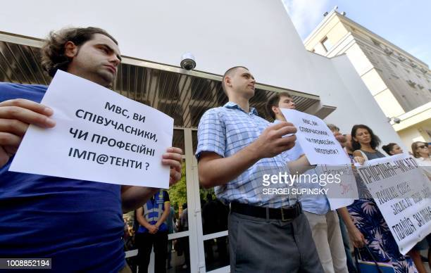 Activists hold placards reading 'Ministry of Internal Affairs are you accomplice or professionally impotent' in front of the Ukrainian Ministry of...