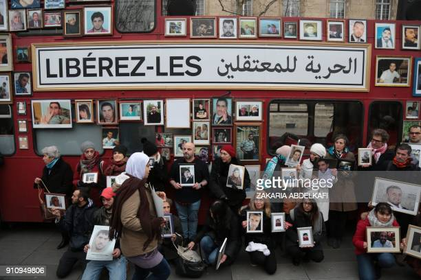 Activists hold portraits of those detained or missing in front of a 'Freedom Bus' after it was driven onto the Place de la Republique in Paris on...