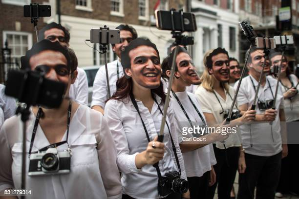 Activists hold selfie sticks as they take 1460 selfies outside the Egyptian Embassy to highlight the plight of jailed Egyptian photojournalist...