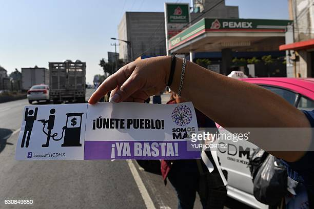 Activists hold signs and shout slogans against the rise in fuel prices while blocking a gas station along Tlalpan avenue during a protest in Mexico...