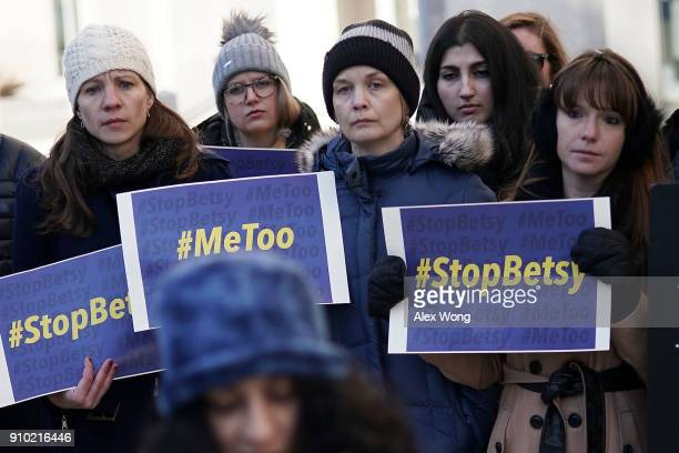 Activists hold signs during a news conference on a Title IX lawsuit outside the Department of Education January 25 2018 in Washington DC Antisexual...