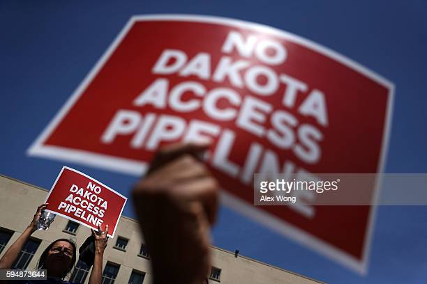 Activists hold signs during a rally on Dakota Access Pipeline August 24 2016 outside US District Court in Washington DC Activists held a rally in...