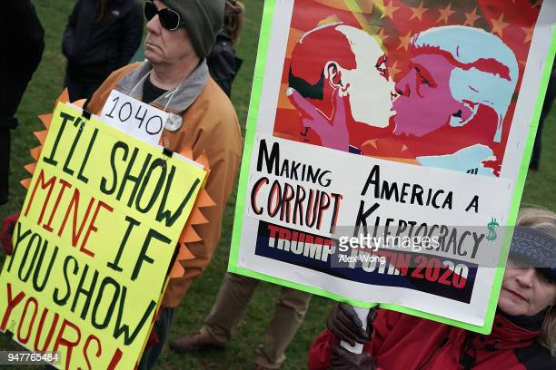 Activists hold signs during a Tax March DC event on the US Capitol East Lawn April 17 2018 in Washington DC Activists gathered on Capitol Hill to...
