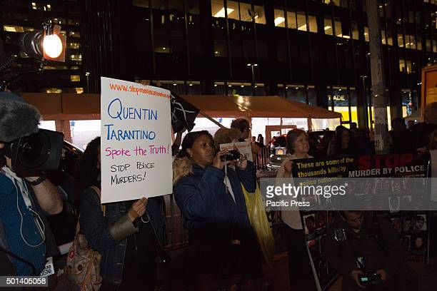 Activists hold signs while rallying behind police barricades opposite the Ziegfeld Theater At the premiere of his new film 'Hateful Eight' at the...