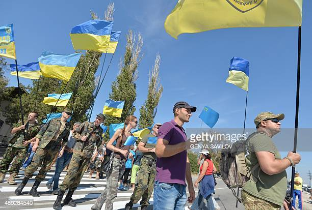 Activists hold Ukrainian and Crimean Tatar flags as they block the road at the checkpoint between Ukraine and Crimea in Chongar on September 20 2015...