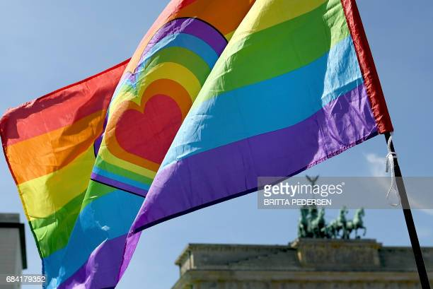Activists hold up a flag with a heart in rainbow colors as they demonstrate against homophobia and transphobia in front of the Brandenburg Gate on...