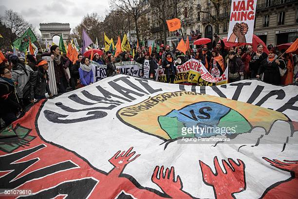 Activists hold up a giant banner reading 'Climate justice' by association 'our power campaign' during a demonstration near the Arc de Triomphe at the...